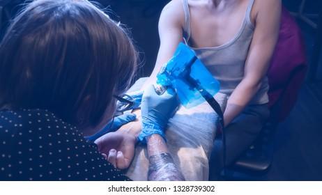 Tattoo artist make tattoo in studio, tattooing on the body. Floral tattoo
