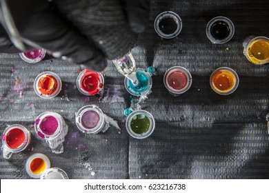 Tattoo artist refilling the pen with blue ink. Overhead shot