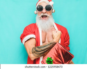 Tattoo fit Santa Clause with gift box wearing funny fest sunglasses  - Fashion senior man with winter holiday costume - Winter, trends, party concept - Soft focus on his mouth