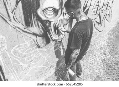 Tattoo graffiti writer painting with color spray his dark picture on the wall - Contemporary artist at work - Urban lifestyle,street art concept - Black and white editing - Vintage retro filter