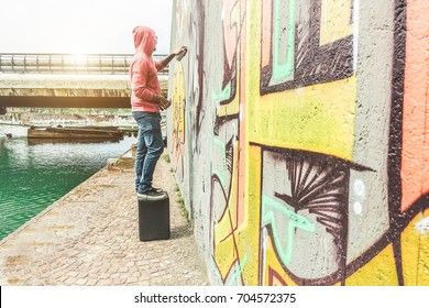 Tattoo graffiti writer painting with color spray on the wall - Focus on him