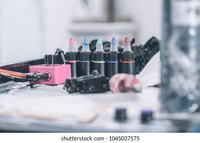 Tattoo machine and bottles with colorful ink