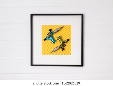 Tattoo machines in frame on white wooden background. Mock up for tattooing artist studio. Flat lay top view copy space