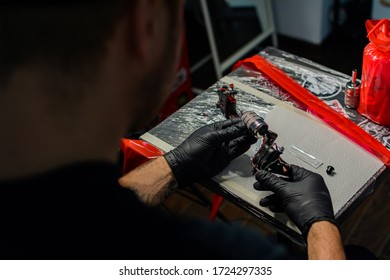 tattoo master in black disposable nitrile gloves prepares a tattoo machine for the session, safety of tattoo procedures, use of disposable materials