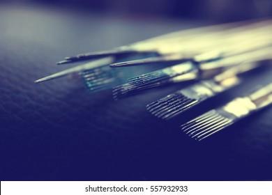 Tattoo needles on dark blurred background, close up view