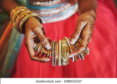 The tattoo on hand of indian bride (mehndi or henna) with bracelets and holding a lot of bracelets (bangle) to be putting on another hand, close-up