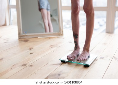 Tattoo on leg. Close up of skinny anorexic woman with tattoo on leg standing on weight scales