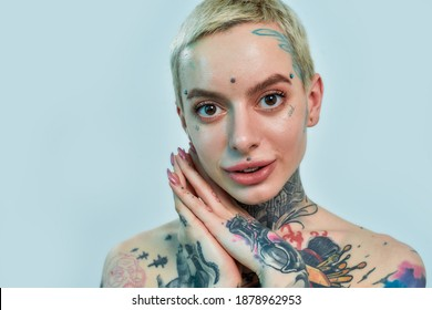 Tattoo and piercing. Close up of a tattooed and pierced white girl wearing denim overall standing and looking into a camera, holdinghands together near face and smiling on a light blue background