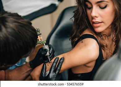 Tattoo. Pretty girl getting a tattoo. Toned image