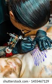 Tattoo salon process. A tattoo girl stuffed a tattoo. the process of stuffing a tattoo on the body. Hands close-up.