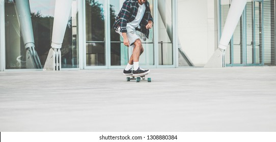 Tattoo skater performing with longboard in urban city contest with offices in background - Young trendy man having fun with skateboard - Extreme sport concept - Focus on shoes board