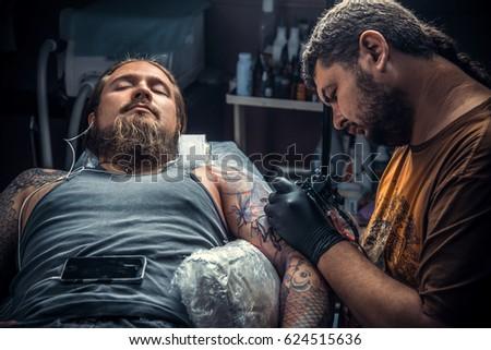 3b6dfa40e Tattoo specialist doing tattoo in tattoo studio./Professional tattooist  makes cool tattoo in studio