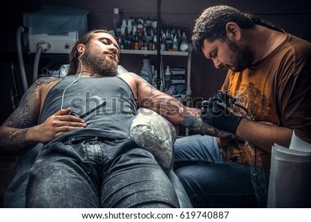 d3f937f90 Tattoo specialist making a tattoo in tatoo salon./Professional tattooist  makes cool tattoo in