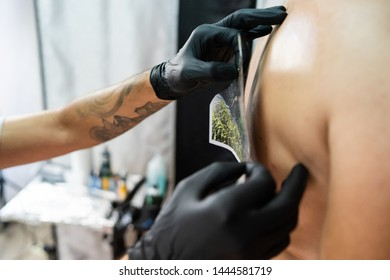 tattoo studio salon preparing for tattooing back tattoo artist master professional copy picture to the customers back