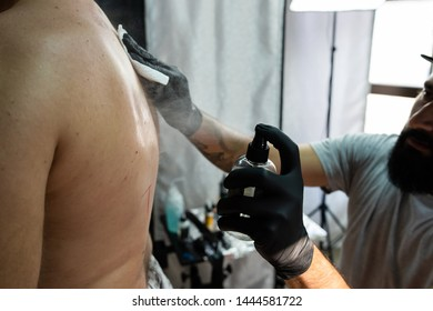 tattoo studio salon preparing for tattooing back tattoo artist master professional applying alcohol to customers back
