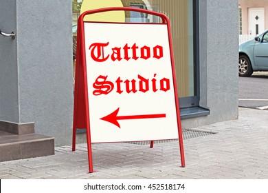 Tattoo Studio  text on pointer billboard near the entrance on german city street