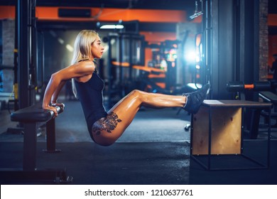Tattooed athlete woman doing push-ups on bench training triceps workout concept fitness, sport