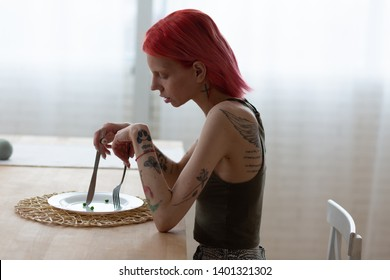 Tattooed back. Anorexic woman with tattooed back and arms sitting in front of empty plate in the kitchen