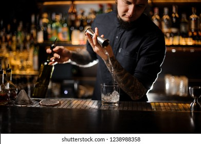 Tattooed bartender pouring an alcoholic drink making a cocktail from the steel jigger to the glass on the bar counter