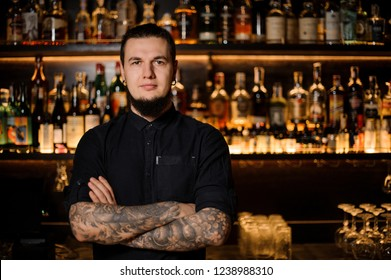 Tattooed bartender standing on the background of the bar shelf with a lot of alcohol bottles