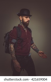 Tattooed bearded man with backpack posing in a studio over dark brown background.