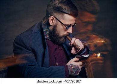 Tattooed bearded man in sunglasses smoking a cigar.