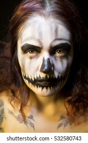 Tattooed beautiful woman in latex and halloween horror makeup in the style of a skeleton skull face