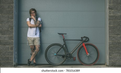 Tattooed biker hipster man in shorts standing next to a fixed gear bike against the background of gray rolling gates