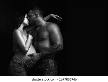 Tattooed boyfriend hugging and kissing pregnant girlfriend. Real romantic passionate moment. Bearded man with tattoo clasping beautiful girlfriend. Emotive of sexy couple