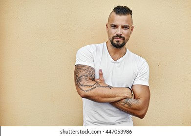 Tattooed brutal man with arms folded wearing white t-shirt - copy space