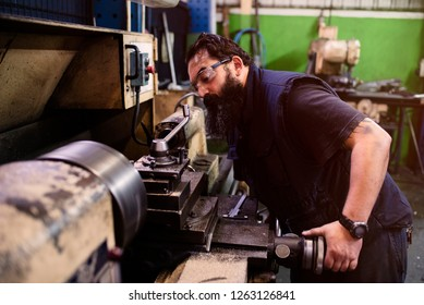Tattooed caucasian man taking working on the lathe in the workshop