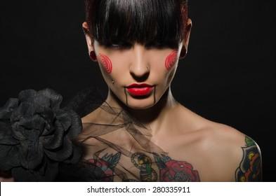 tattooed charming brunette with black flower on dark background