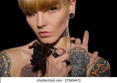 tattooed charming woman with tattoo machine, dark background