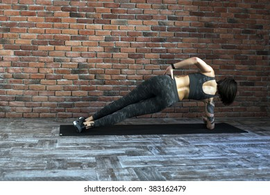 tattooed female doing exercises indoors, sporty woman practicing yoga