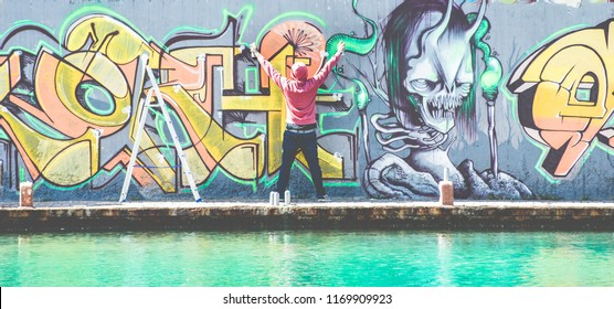 Tattooed graffiti writer finishing with color spray his picture on the wall - Contemporary artist at work - Urban lifestyle, youth, millennial generation and street art concept - Focus on guy head