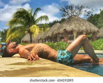 Tattooed guy lying by the pool