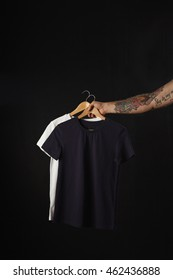 Tattooed hand holds black and white basic blank t-shirts isolated on black