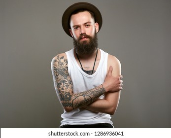 Tattooed handsome Bearded Man in Hat. Brutal hipster boy with tattoo