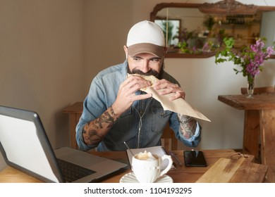 Tattooed hipster with beard watching laptop in cafeteria while taking bite of delicious snack