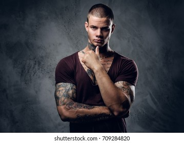 Tattooed male with crossed arms over grey artistic background.