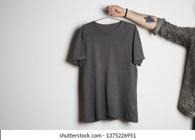 Tattooed male hand holds hang with blank gray t-shirt from premium thin cotton on white background. Mockup Copy Paste Advertisement