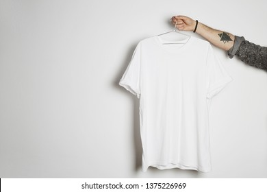 Tattooed male hand holds hang with blank white t-shirt from premium thin cotton on white background. Mockup Copy Paste Advertisement