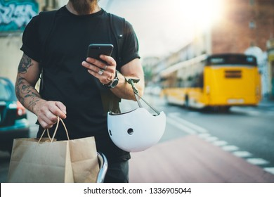 Tattooed Man courier using a map app on mobile phone to find the delivery address in the city.Courier bicycle delivery food service at home