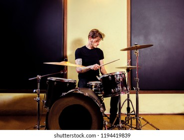 Tattooed man playing drums in studio