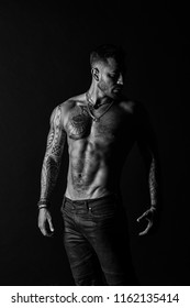 Tattooed man show sexy muscular torso. Sportsman with six pack and ab. Bodybuilder with biceps and triceps. Fashion model with tattoo in jeans. Bodycare with fitness and sport, black and white.