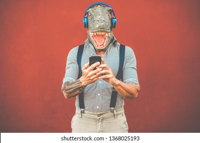 Tattooed man with t-rex mask using smartphone while listening music - Crazy senior guy choosing playlist from mobile phone app - Technology trends and madness costume concept - Focus on face