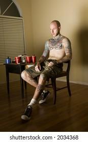 tattooed man watching TV