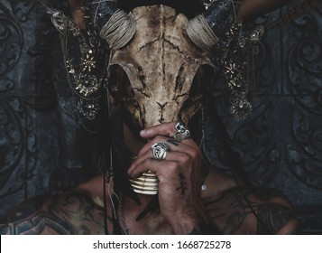 Tattooed masked skull ethnic pagan shaman sit on stage an ancient temple
