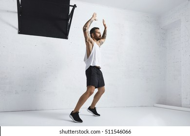 Tattooed and muscular athlete doing jumping jacks isolated on white brick wall next to black pull bar, looking right side