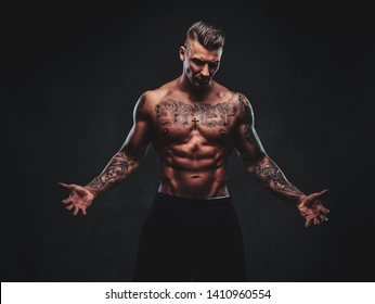 A tattooed muscular shirtless man with stylish hair posing at the camera on a dark background.